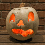 Lit white jack o'lantern on a bench Stock Images