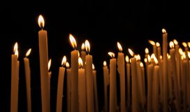 Lit yellow candles on a dark background stock image