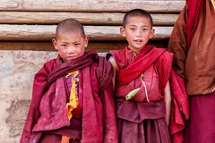 LITANG and GANZI, CHINA - MAY 02, 2016 : Unidentified two little boys smiling of buddhist novice monks are praying in Boudhanath m stock photography