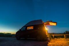 LITAUEN - Augusti 2018: Vw-biltransport T4 under natten på en tältplats i Lettland med ljus inom Sikt in mot fotografering för bildbyråer