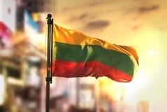 Litauen flagga mot suddig bakgrund för stad på soluppgång Backli Royaltyfria Foton