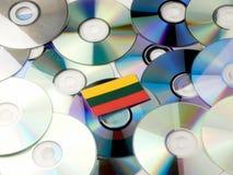 Litauisk flagga överst av CD- och DVD-högen som isoleras på vit Royaltyfri Foto