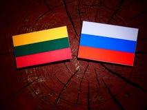 Litauisk flagga med den ryska flaggan på en trädstubbe Royaltyfri Foto
