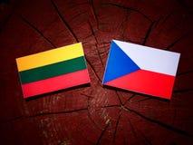 Litauisk flagga med den tjeckiska flaggan på en trädstubbe Fotografering för Bildbyråer