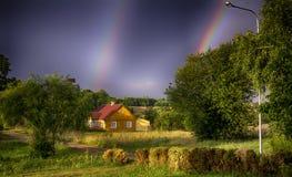 Litauiskt lantligt gammalt gult hus, regnbåge Arkivbilder