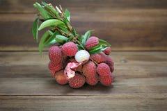 Litchi chinensis owoc z liśćmi strugającymi pokazywać ciało biel na drewnianym tle obrazy royalty free