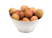 Litchi fruits in round bowl isolated on white closeup Stock Photos