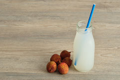 Litchi juice in a glass bottle  and fresh litchis Stock Images