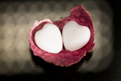 Litchi peel with heart shaped agate on black Stock Photo