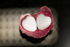 Litchi peel with heart shaped agate on black Royalty Free Stock Image