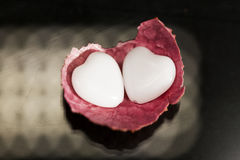 Litchi peel with heart shaped agate on black Stock Photography