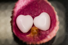Litchi peel with heart shaped agate on black Stock Images