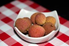 Litchiplommoner i en vit liten röd och vit bordduk för maträtt - Royaltyfri Fotografi