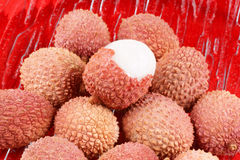 Litchis or lychees. Close-up of some litchis (lychee) on a glass plate over a red background Stock Photos