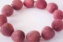 Litchis on white background. Whole litchis in a circle on white background Royalty Free Stock Photos