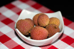 Litchis in a white small dish - red and white tablecloth Royalty Free Stock Photography