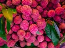Litchivruchten achtergrond, Vers litchi en gepeld tonend de rode huid en het witte vlees met groen blad Verkoop op de markt in Th royalty-vrije stock foto's