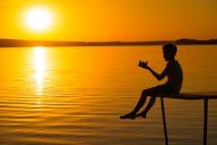 Lite är barnet på en bro med origami i formen av ett fartyg i hans händer på solnedgången Benen av barnet fällde ned arkivfoton