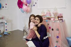Lite är flickan i ett rosa omslag och en pulverkjol kramar hennes mo Royaltyfria Bilder