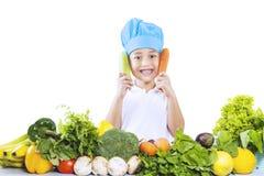 Kockpojke med grönsaker på vit Arkivfoto