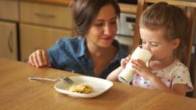 Lite äter flickan förvanskade ägg Mamman matar henne med en gaffel Båda flickor är jätteglade arkivfilmer
