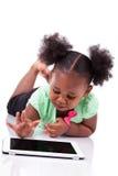 Lite afrikansk amerikanflicka som använder en tabletPC arkivfoton