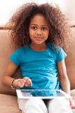 Lite afrikansk asiatisk flicka som använder en tabletPC arkivfoto