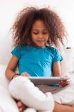 Lite afrikansk asiatisk flicka som använder en tabletPC Arkivbilder