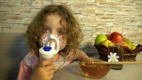 Lite använder flickan en nebulizer arkivfilmer