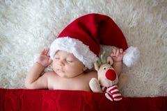 Lite att sova som är nyfött, behandla som ett barn pojken som bär jultomtenhatten arkivfoto