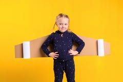 Lite bär barnflickan hemlagade pappflygvingar som låtsar för att vara en pilot för ett hantverk, fantasi eller Royaltyfria Foton
