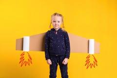Lite bär barnflickan hemlagade pappflygvingar som låtsar för att vara en pilot för ett hantverk, fantasi eller Royaltyfri Foto