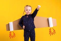 Lite bär barnflickan hemlagade pappflygvingar som låtsar för att vara en pilot för ett hantverk, fantasi eller Royaltyfria Bilder