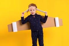 Lite bär barnflickan hemlagade pappflygvingar som låtsar för att vara en pilot för ett hantverk, fantasi eller Arkivbild