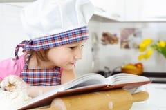 Lite bagare i hatten som förbereder kakor med kokbok arkivfoton