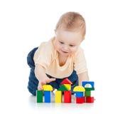 Lite barn som leker med byggande kvarter Arkivbild