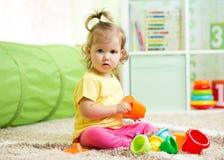 Lite barn som leker med toys Arkivfoton