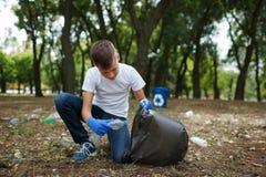 Lite barn som upp väljer avskrädet och sätter den i en svart avskrädepåse på en naturlig bakgrund Ekologiskydd arkivbild
