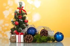 Lite beautifully dekorerad julgran, gåvor, kottar, leksak-ballonger, på gul bakgrund Royaltyfri Bild