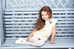 Lite bidar flickan av sju år med kastanjebrunt hår, ställningar bredvid en träbänk och enblått fönsterramen med blommor som in le Fotografering för Bildbyråer