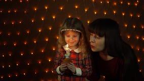 Lite blåser flickan ut en stearinljus på en festlig kaka med hennes mamma stock video