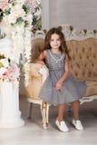 Lite blommar flickan av sju år med brunt hår som sitter bredvid en bukett av pionen och att le, i en grå klänning i en bur, krull Arkivbilder