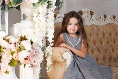 Lite blommar flickan av sju år med brunt hår som sitter bredvid en bukett av pionen och att le, i en grå klänning i en bur, krull Royaltyfri Foto