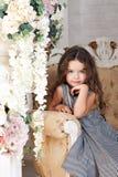Lite blommar flickan av sju år med brunt hår som sitter bredvid en bukett av pionen och att le, i en grå klänning i en bur, krull Fotografering för Bildbyråer