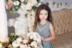 Lite blommar flickan av sju med kastanjebrunt hår, ställningar bredvid en bukett av pionen och att le, i en grå klänning i en bur Royaltyfria Bilder