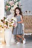 Lite blommar flickan av sju med kastanjebrunt hår, ställningar bredvid en bukett av pionen och att le, i en grå klänning i en bur Arkivbild