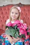 Lite blond flicka i färgrikt klänningsammanträde på den stora röda soffan fotografering för bildbyråer
