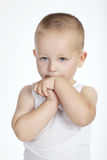 Lite blyg pojke på vit bakgrund Arkivfoton