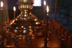 Lite brännande kyrkastearinljus mot en mörk bakgrund, closeup Royaltyfri Fotografi