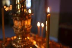 Lite brännande kyrkastearinljus mot en mörk bakgrund, closeup Arkivfoton